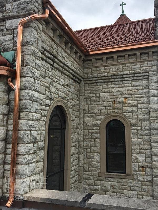 copper gutter and downspout, with a stone wall and red clay tile roof