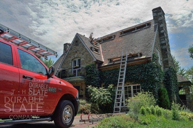 durable slate truck parked in front of a slate roofed house under repair