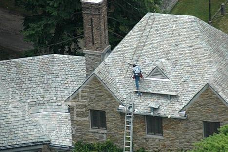 another view of durable workers repairing a large slate roof