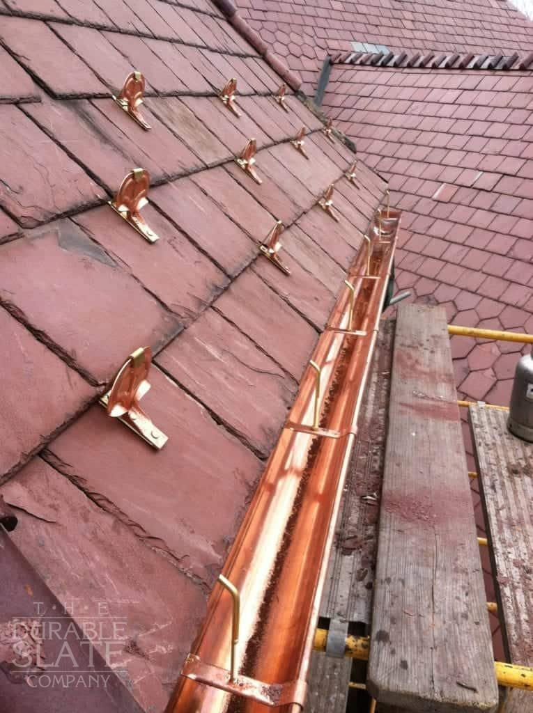 new copper gutters alongside older red slate roof