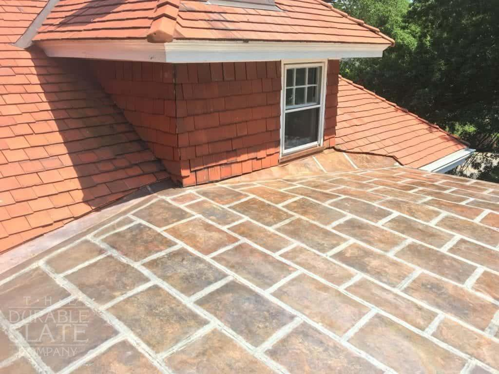 a copper flat lock roof with terra cotta clay-tile roof