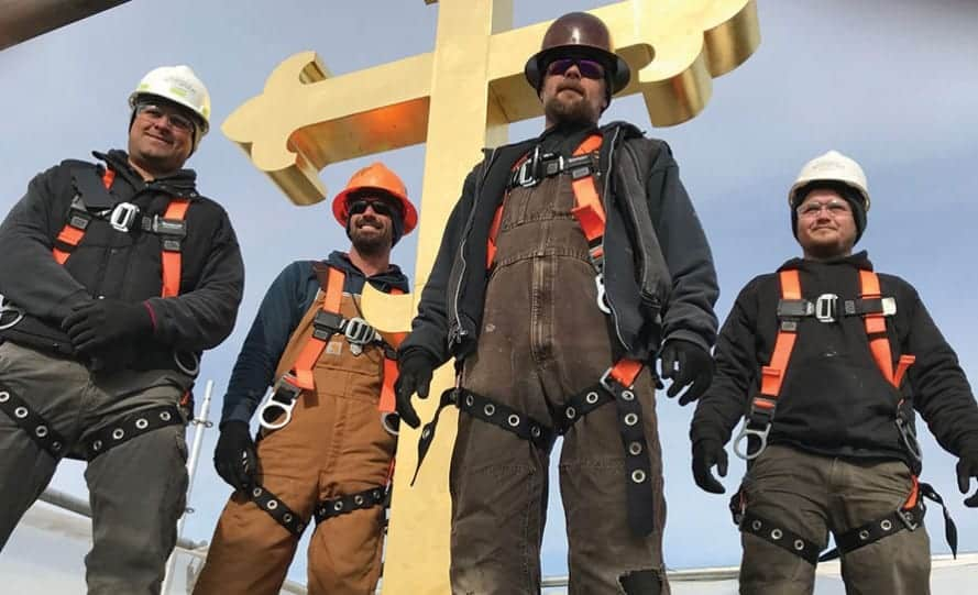 durable slate and restoration employees standing in front of steeple square copper cross